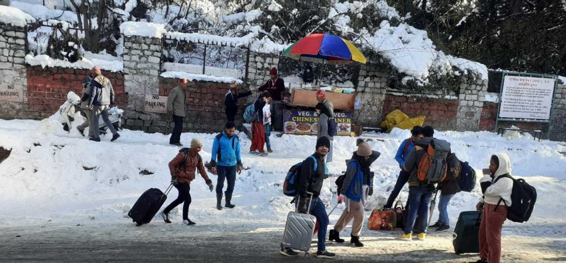 Tourists struggle to walk on slippery ice on road
